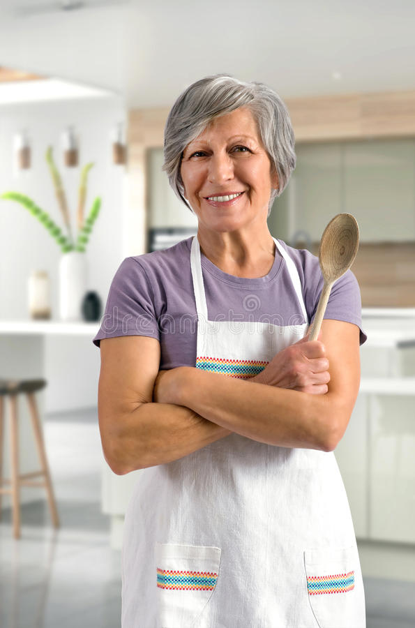 Happy friendly senior woman baking in the kitchen stock photography