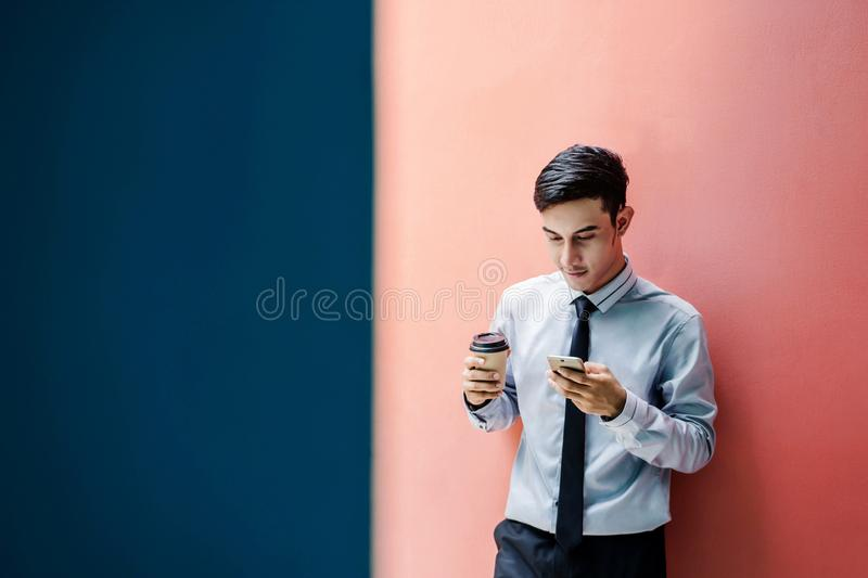 Happy and friendly young attractive Businessman use a Smart phone at colorful wall, Social communicate technology in business con royalty free stock image