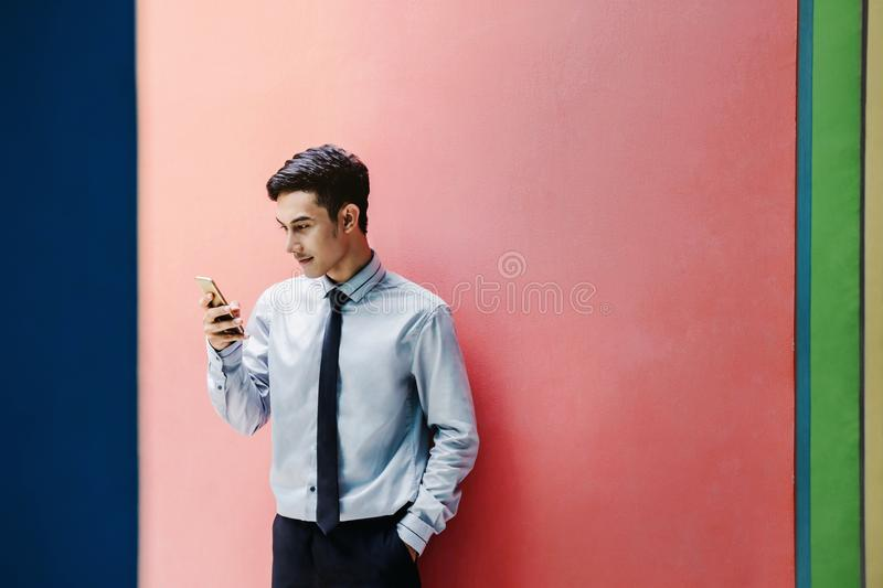 Happy and friendly young attractive Businessman use a Smart phone at colorful wall, Social communicate technology in business con. Cept, Lifestyle of modern male stock images