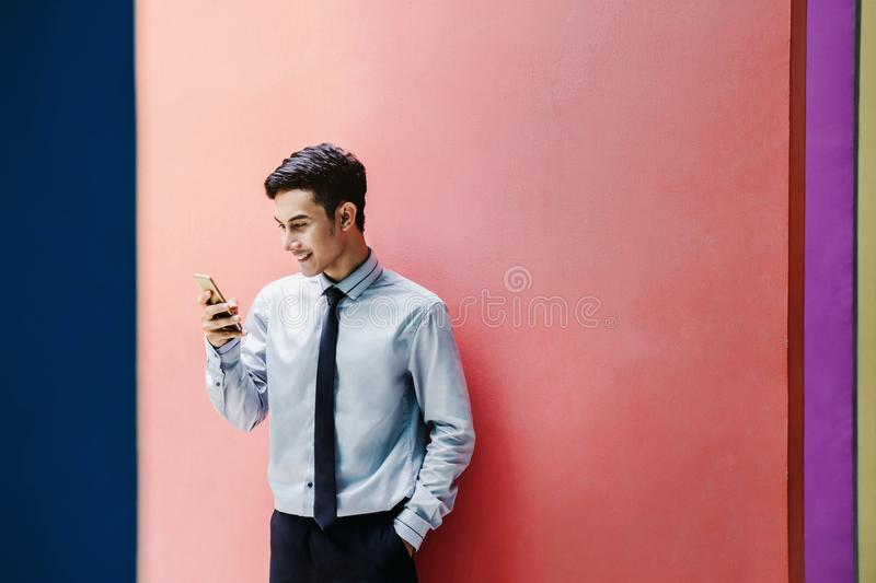 Happy and friendly young attractive Businessman use a Smart phone and holding morning coffee at colorful wall, Social communicate. Technology in business stock photos