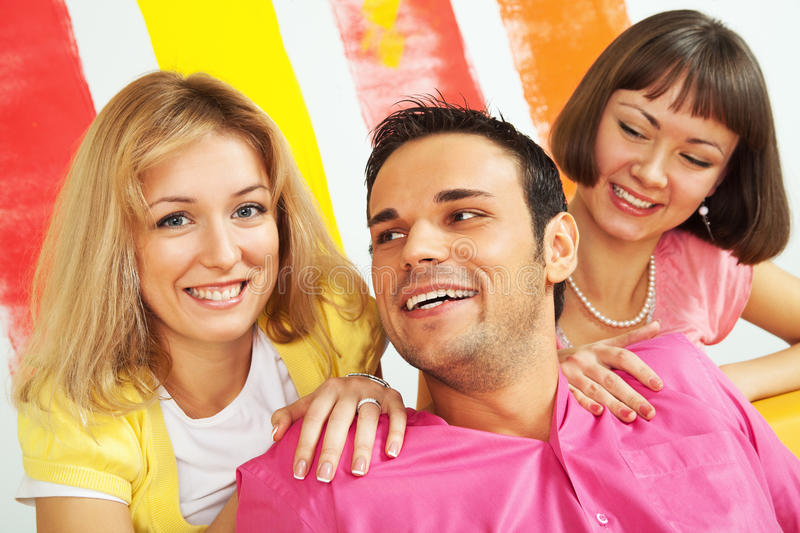 Happy friends. Group of three happy people sitting on sofa in a colorfully painted room stock image