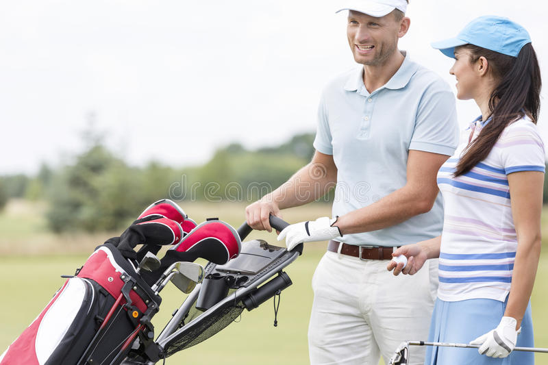 Happy friends with bag talking at golf course royalty free stock images