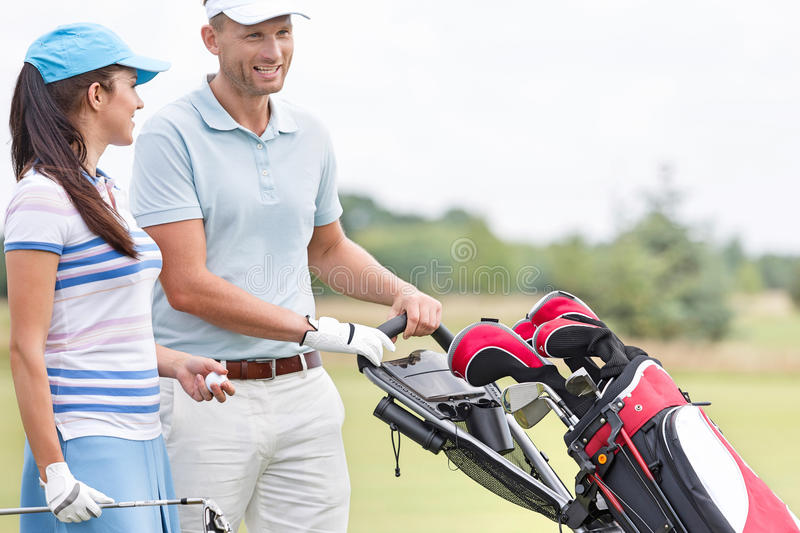 Happy friends with bag talking at golf course royalty free stock photos