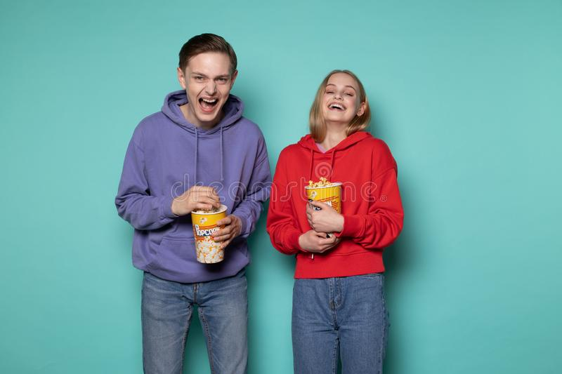 Happy friends, beautiful blonde girl and guy in purple hoodie watching a comedy movie with popcorn in hands stock images
