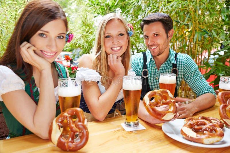 Happy friends in beer garden royalty free stock image