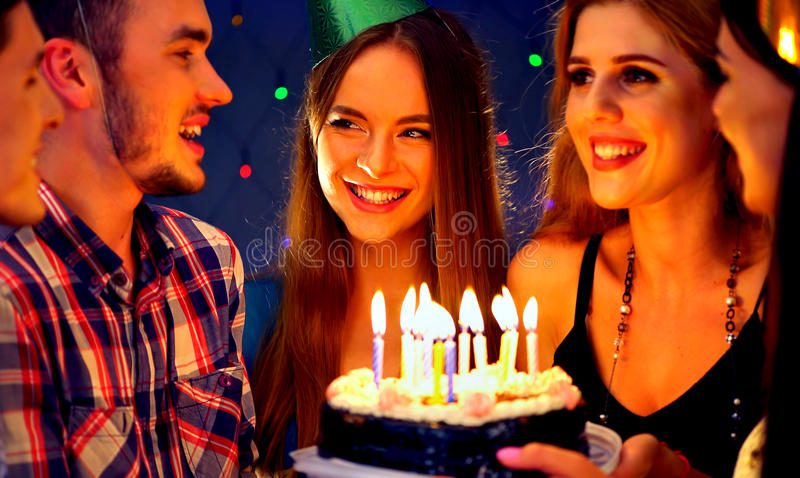 Happy friends birthday party with candle celebration cakes in club. Happy friends birthday celebrating food with candle celebration cakes in club. People wear stock photo
