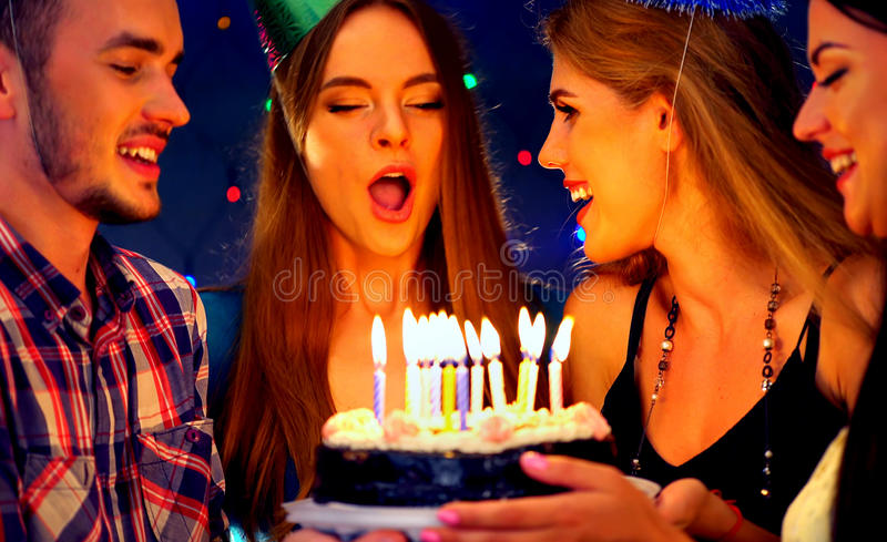 Happy friends birthday party with candle celebration cakes. People looking at burning candles. Girl in hat blows out . Women and men have fun stock image