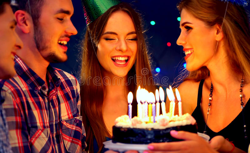 Happy friends birthday party with candle celebration cakes. People looking at burning candles. Girl in hat blows out. Women and men have fun on dark background stock images