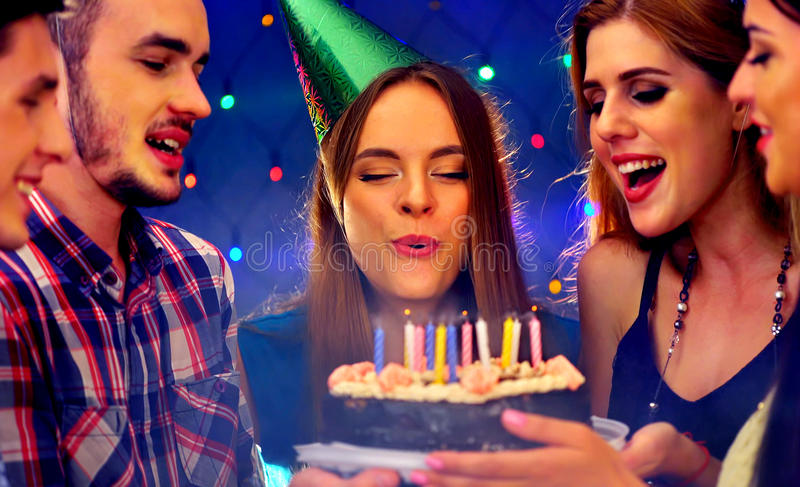 Happy friends birthday party with candle celebration cakes. People looking at burning candles. Two women and men have fun in nightclub royalty free stock images