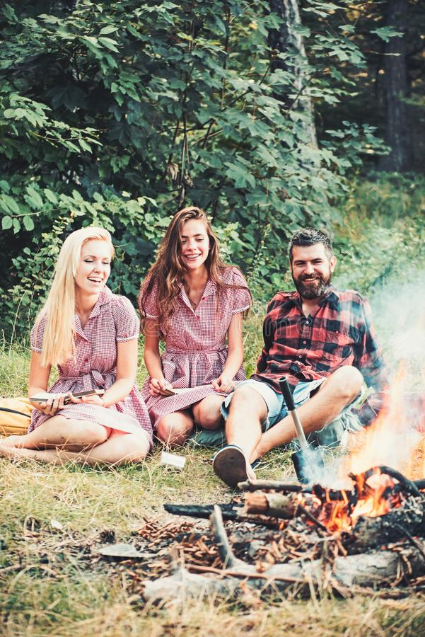 Happy friends at campfire. Bearded man and women smile at bonfire. Hipster in palid shirt and girls in vintage dresses royalty free stock images