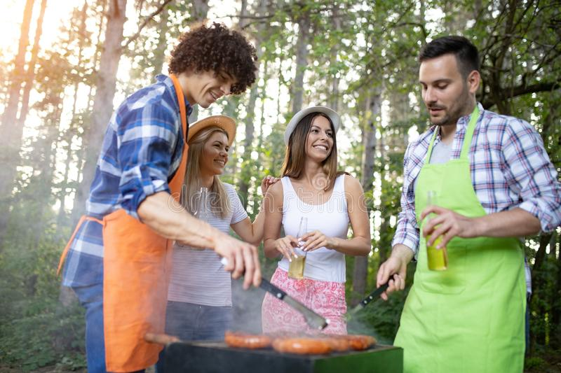 Happy friends camping and having a barbecue in nature stock images