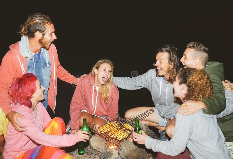 Happy friends camping together and cooking corn at night outdoor - Young people having fun and laughing around bonfire royalty free stock image
