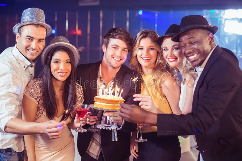 Happy friends celebrating birthday with cake. In night club royalty free stock photography
