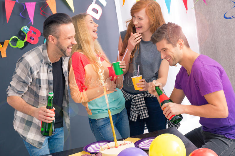 Happy friends celebrating birthday. Drinking champagne from party cups royalty free stock photos