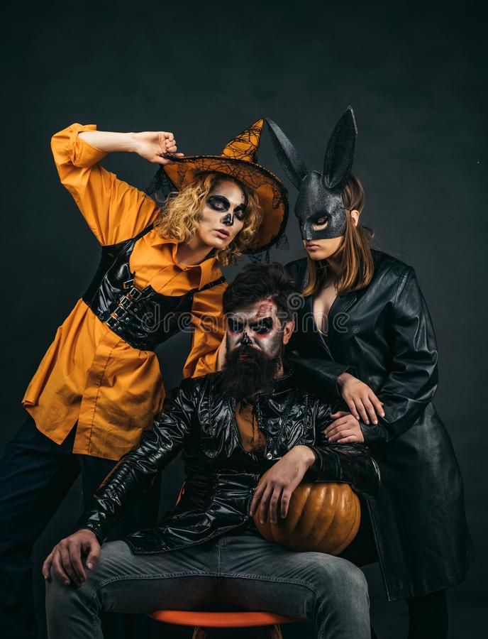 Happy friends celebrating Halloween. Close up Halloween portrait of funny group. Surprised group of friends in witch hat royalty free stock images
