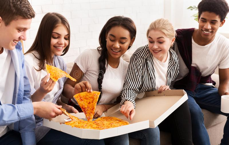 Happy friends celebrating meeting, eating hot pizza stock photo