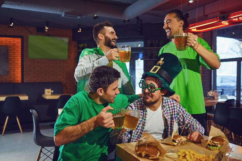 Happy friends celebrating St. Patrick`s Day in a bar. royalty free stock image