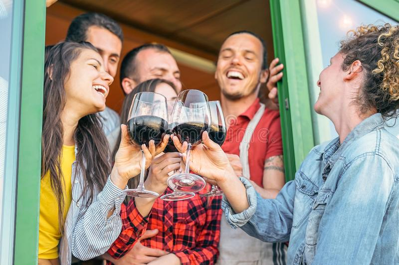 Happy friends cheering with glasses of red wine in terrace - Young people having fun drinking, toasting and laughing together royalty free stock images