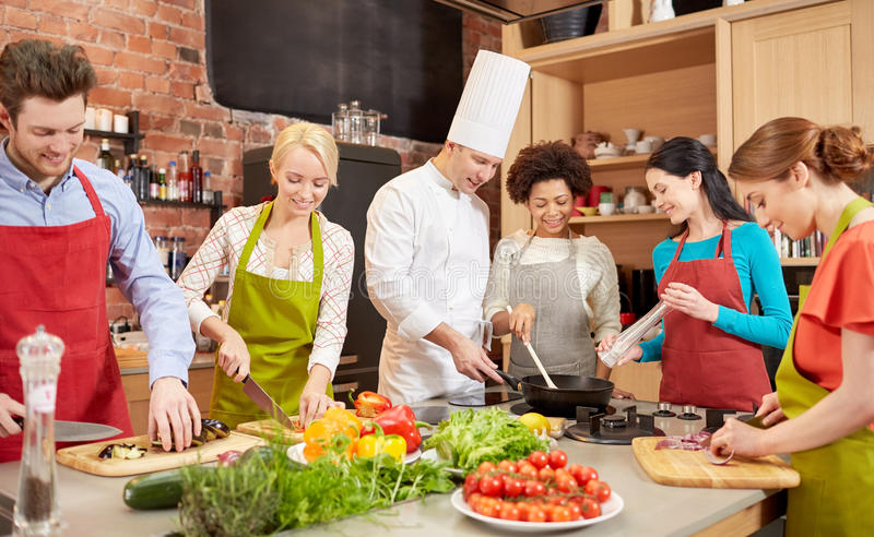Happy friends and chef cook cooking in kitchen. Cooking class, culinary, food and people concept - happy group of friends and male chef cook cooking in kitchen royalty free stock photo