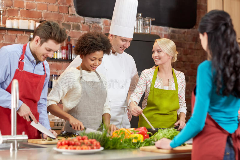 Happy friends and chef cook cooking in kitchen. Cooking class, culinary, food and people concept - happy group of friends and male chef cook cooking in kitchen royalty free stock photos