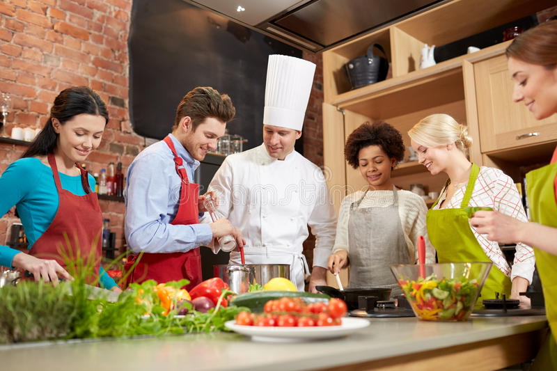 Happy friends and chef cook cooking in kitchen. Cooking class, culinary, food and people concept - happy group of friends and male chef cook cooking in kitchen stock image