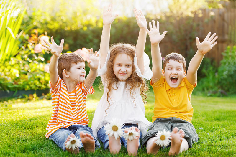 Happy friends children with daisy flowers at green grass in a summer park. royalty free stock image