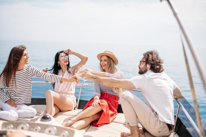 Happy friends clinking glasses of champagne and sailing on yacht stock images