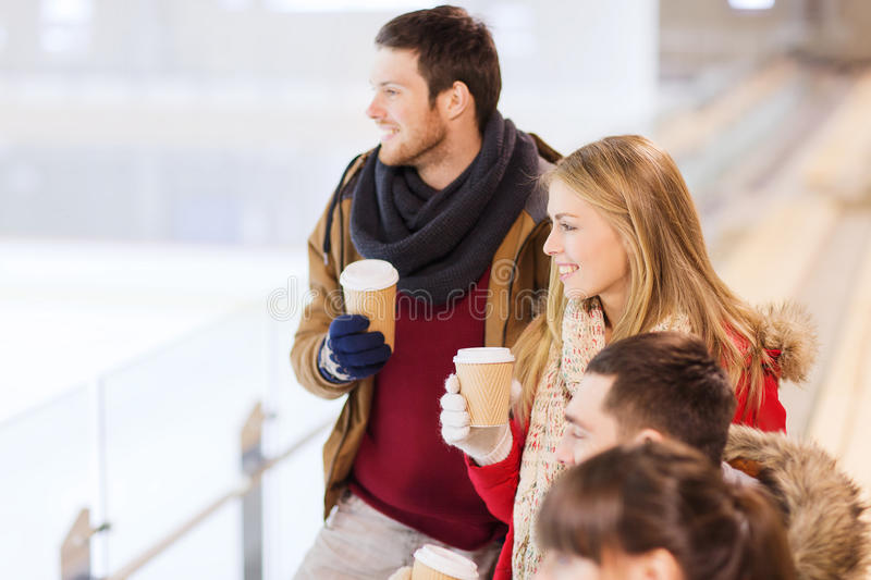 Happy friends with coffee cups on skating rink. People, friendship, hot drinks and leisure concept - happy friends drinking from paper coffee cups on skating royalty free stock photo