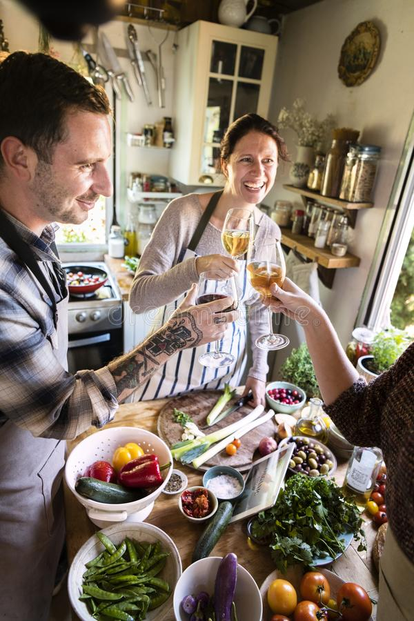 Happy friends cooking together in the kitchen royalty free stock photography