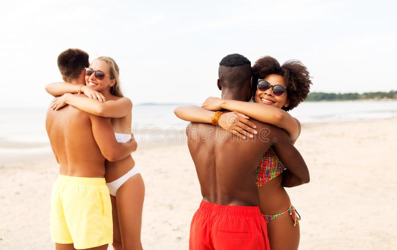Happy friends or couples hugging on summer beach royalty free stock photos
