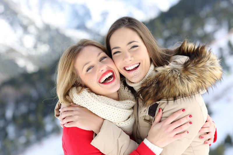 Happy friends cuddling and posing in winter holiday. In a snowy mountain stock photos