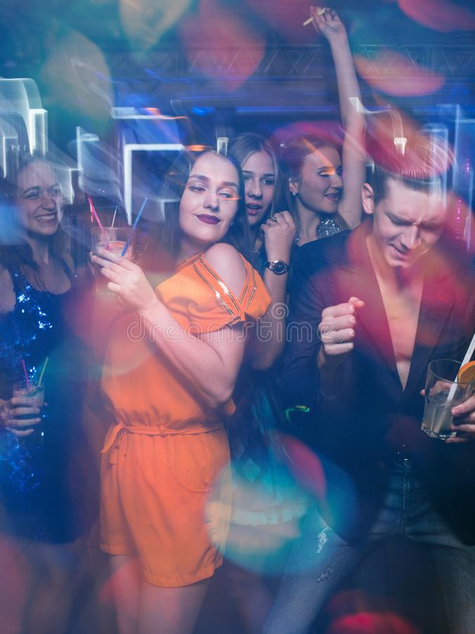 Happy friends dance in motion. Joyful New Year company in night club, active Christmas celebration. Disco party in blurred colors, modern youth life royalty free stock image