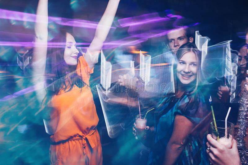 Happy friends dance party in motion. Joyful New Year company in night club, active Christmas celebration. Disco people in blurred colors, modern youth life royalty free stock photography