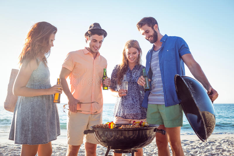 Happy friends doing barbecue and drinking beer. At the beach stock photography
