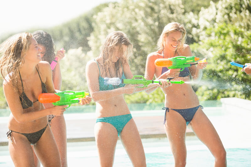 Happy friends doing water gun battle stock photo