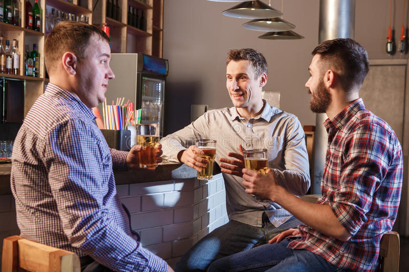 Happy friends drinking beer at counter in pub. Happy smiling friends drinking beer at counter in pub royalty free stock image