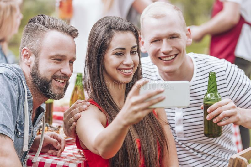 Happy friends drinking beer and taking selfie during grill party. Photo concept stock photo