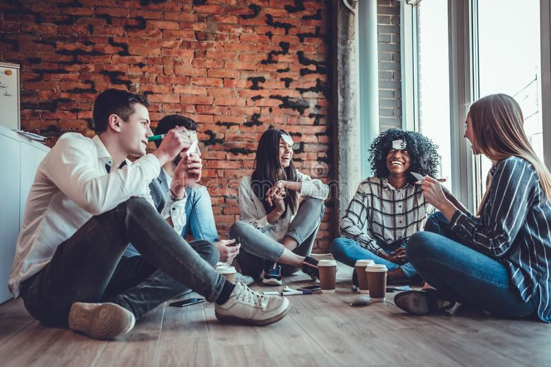Happy friends drinking coffee and playing game guess who while having fun at home stock photo