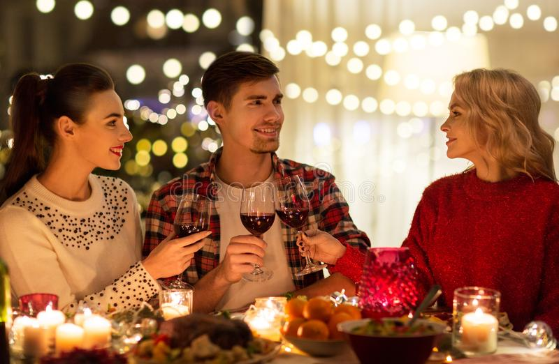 Happy friends drinking red wine at christmas party stock photo
