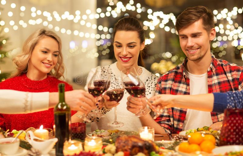 Happy friends drinking red wine at christmas party royalty free stock photo