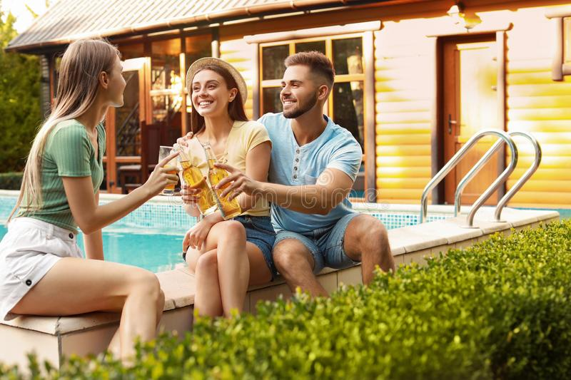 Happy friends with drinks at barbecue party near swimming pool royalty free stock photos
