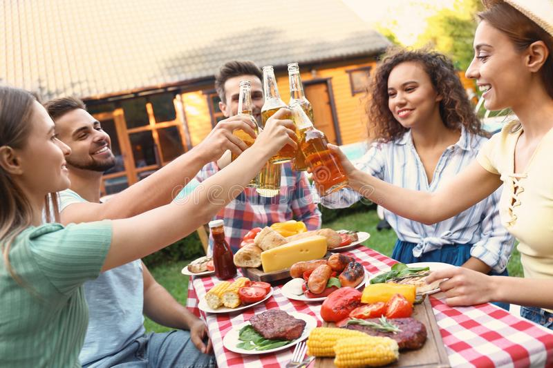 Happy friends with drinks having fun at barbecue party royalty free stock photo