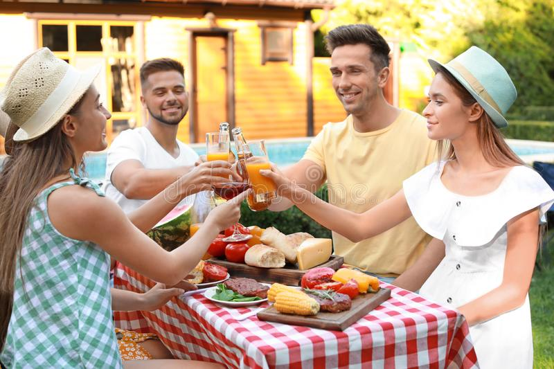 Happy friends with drinks having fun at barbecue party stock image