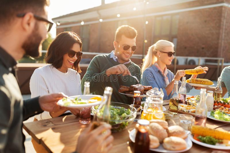 Happy friends eating at barbecue party on rooftop stock image