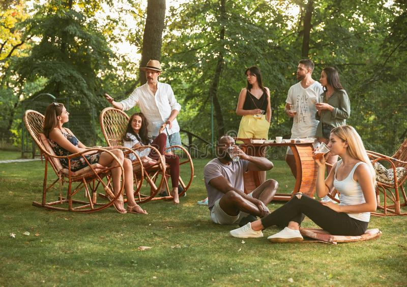 Happy friends eating and drinking beers at barbecue dinner on sunset time royalty free stock photos