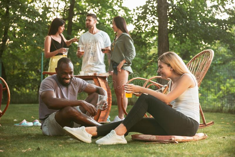 Happy friends eating and drinking beers at barbecue dinner on sunset time royalty free stock photography
