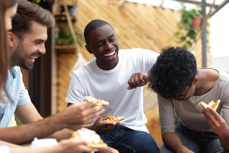 Happy friends eating pizza together, laughing at funny joke stock photo