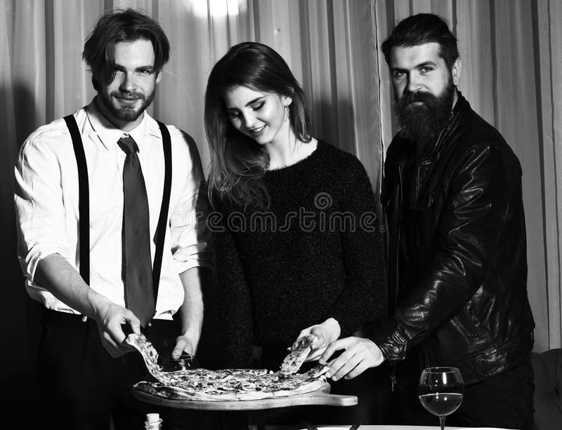 Happy friends eating tasty pizza. Happy friends, pretty girl and two bearded men, hipsters with beards, smiling and eating tasty pizza served on wooden tray at stock image
