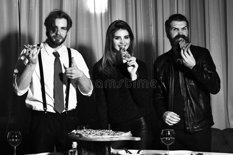 Happy friends eating tasty pizza slices. Happy friends, pretty girl and two bearded men, hipsters with beards, smiling and eating tasty pizza slices at party in stock images