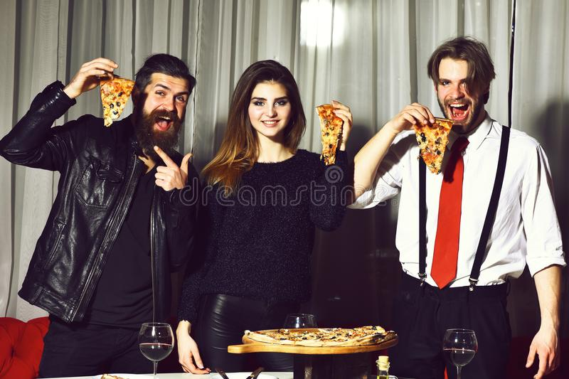 Happy friends eating tasty pizza slices with thumbs up gestures royalty free stock images